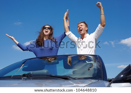 Young couple stands, raising their hands in cabriolet and shouts on background of blue sky - stock photo