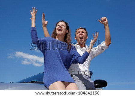 Young couple stands, raising their hands in cabriolet and shouts on background of bright blue sky - stock photo