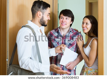 Young couple stands with realtor in the doorway looking round new flat