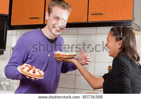 Young couple starting a cream pie fight in the kitchen - stock photo