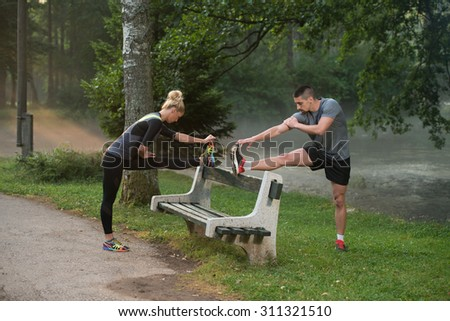 Young Couple Stretching Before Running In Wooded Forest Area - Training And Exercising For Trail Run Marathon Endurance - Fitness Healthy Lifestyle Concept - stock photo