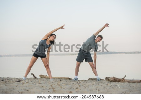 Young couple stretching on beach