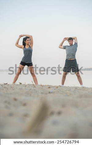 Young couple stretching on beach - stock photo