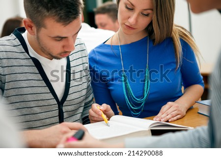 Young couple students studying at the classroom - stock photo