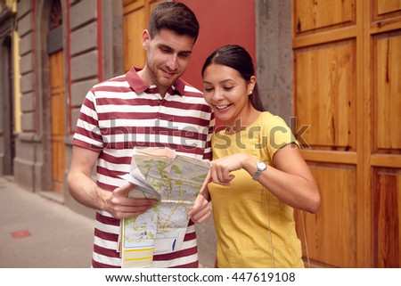 Young couple studying a map and pointing at it while smiling happily and dressed casually in t-shirts with old buildings behind them