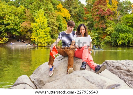 Young couple studying outside by a lake, guy wearing a striped t shirt, brown pants, sneakers, holding a book, girl dressing in white top, red pants, boot shoes, reading on laptop computer. Outing. - stock photo