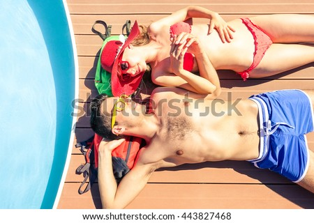Young couple sun tanning at pool deck of cruise ship - Beautiful lovers holding hands lying on yacht poolside - Concept of unforgettable love moment on the honeymoon vacation - Soft vintage filter - stock photo