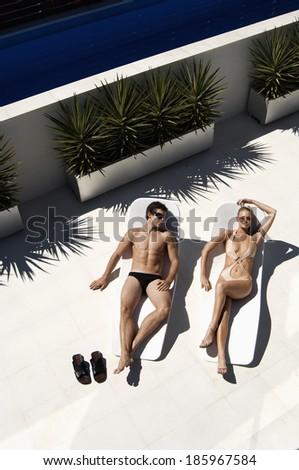 Young Couple Sunbathing on Lounge Chairs - stock photo