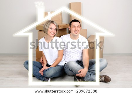 Young couple surrounded by form of house - stock photo