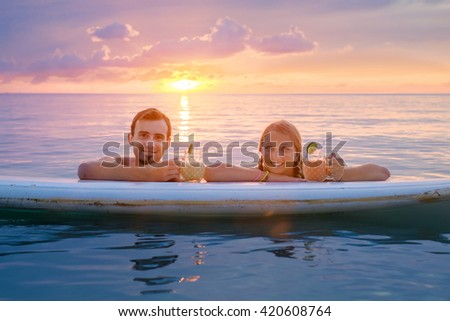 Young couple swiming with paddle board in the sea  at sunset and drinking fruit cocktails - stock photo