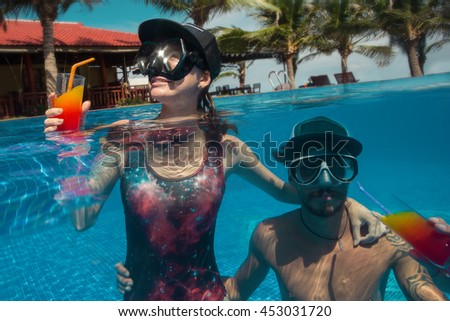 Young couple swimming in swimming pool with cocktails and have a fun at resort. - stock photo