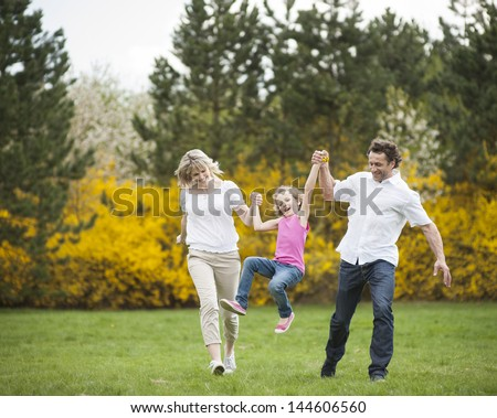 Young couple swinging daughter between them - stock photo