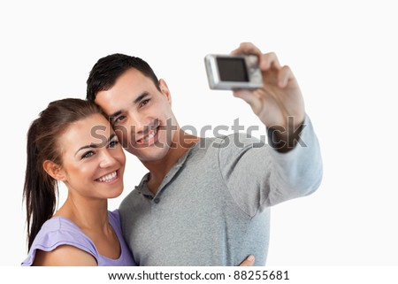 Young couple taking a picture of themselves against a white background
