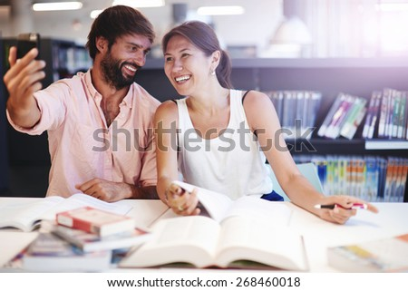 Young couple taking a self portrait in light interior,two beautiful teens posing for a selfie while sitting in light library preparing for exams, young students taking a photo of themselves in library - stock photo