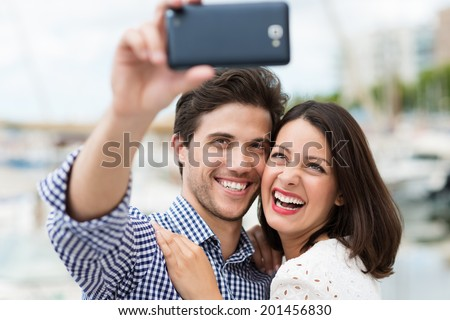 Young couple taking a self portrait laughing as they pose close together for the camera on their smartphone outdoors in summer sunshine - stock photo
