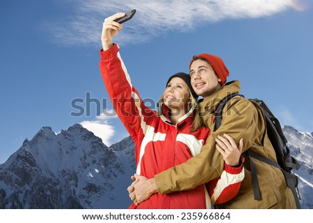 young couple taking a selfie during wintersports of a magnificent view over an alpine mountain rainge - stock photo