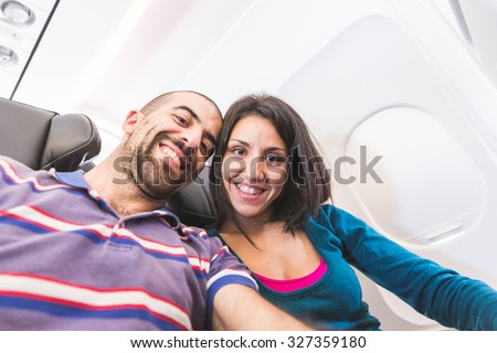 Young couple taking a selfie on the airplane. They are a man and a woman, smiling and looking at camera. Travel and lifestyle concepts. - stock photo