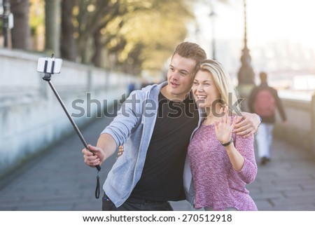 Young couple taking a selfie with smartphone on the stick. The man is holding the stick and embracing the girl, she is waving while looking at phone. Backlight flare added. - stock photo