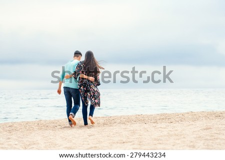 Young couple taking a walk on beach on cloudy day. Couple walking along seamless clouds and water giving back. - stock photo