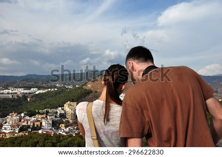 Young couple taking photo of Malaga cityscape from Alcazaba Castle.