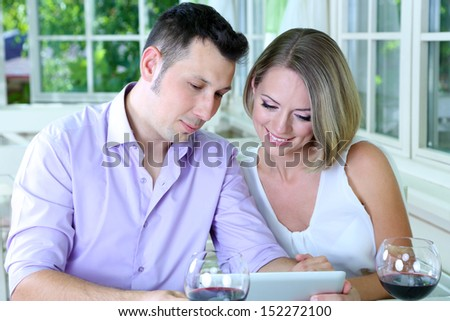 Young couple  taking photo with tablet in restaurant