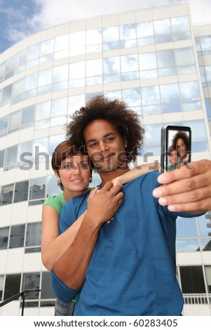 Young couple taking picture of itself with mobile phone - stock photo