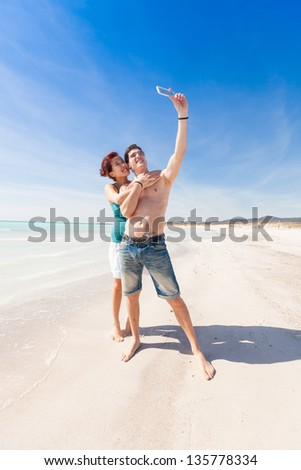Young Couple Taking Self Portrait with Mobile at Beach - stock photo