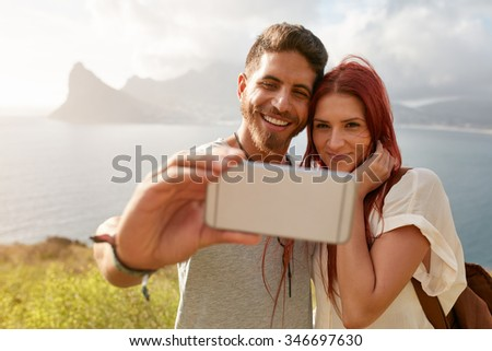 Young couple taking self portrait with mountain and bay scenery in background. Caucasian young man taking selfie with his smart phone outdoors. - stock photo
