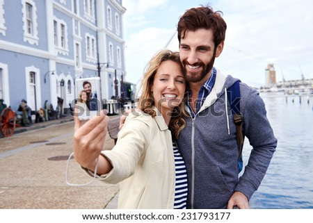 young couple taking selfi on vacation at the waterfront area near the ocean