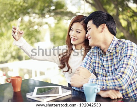 young couple taking selfie in coffee shop. - stock photo