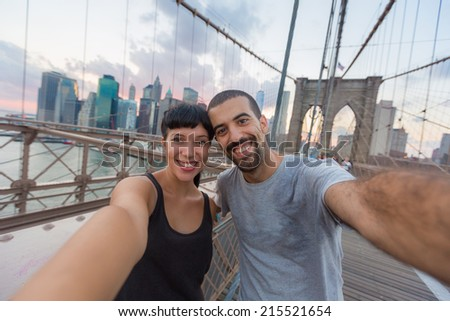 Young Couple Taking Selfie on Brooklyn Bridge - stock photo