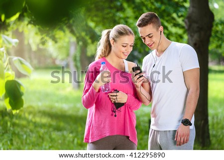 Young couple talking in the park after jogging. Having a great time together.