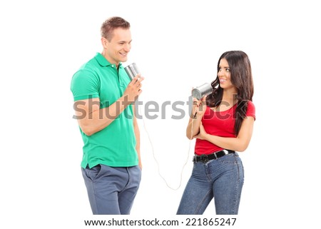 Young couple talking through a tin can phone isolated on white background