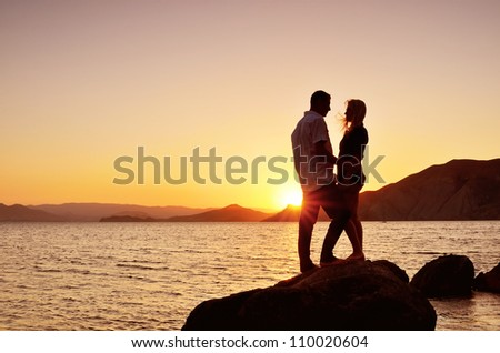 Young couple talking to the sea at night - stock photo