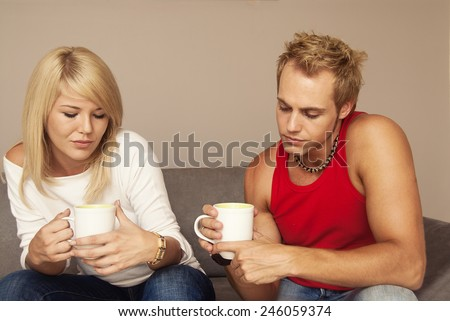 Young couple talking while drinking coffee - stock photo