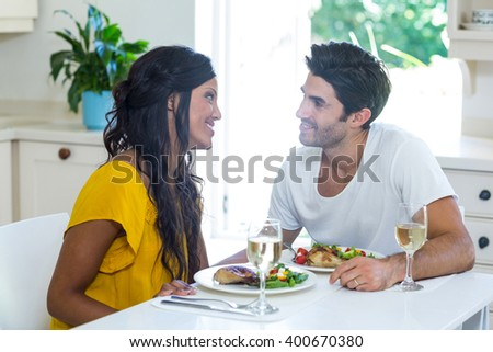 Young couple talking while having meal in kitchen at home - stock photo