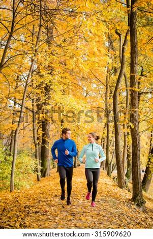 Young couple talking while jogging together in beautiful autumn nature - stock photo