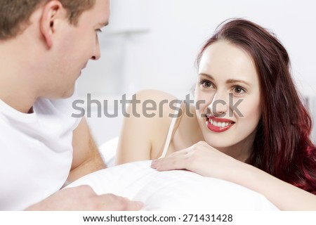 Young couple talking while lying in bed in the morning - stock photo