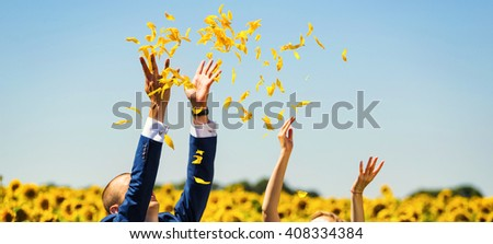 Young couple throwing sunflower petals in the field - stock photo