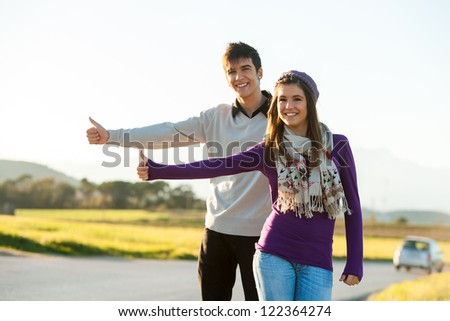 Young couple thumb riding along sunny country road. - stock photo