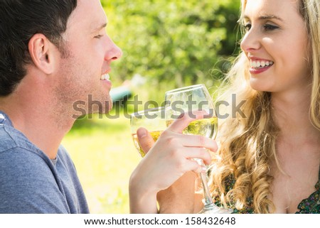 Young couple toasting and linking arms while looking at each other outside - stock photo