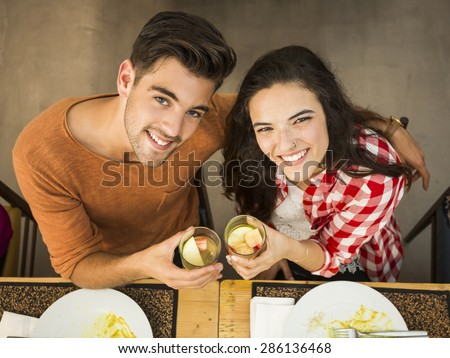 Young couple toasting and looking happy at a restaurant - stock photo