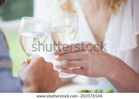 Young couple toasting with white wine at home in the dining room
