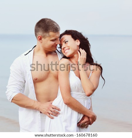 young couple together against sea.