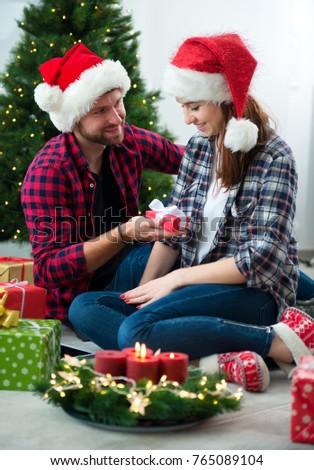 Young couple together celebrating Christmas at decorated home