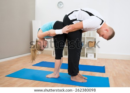 Young Couple Together Exercising On Blue Mat At Home - stock photo