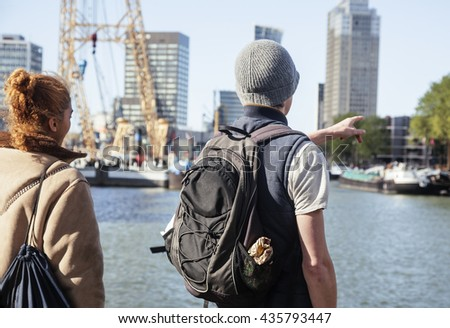 Young couple tourists looking and pointing to Rotterdam city harbour, future architecture concept, industrial lifestyle
