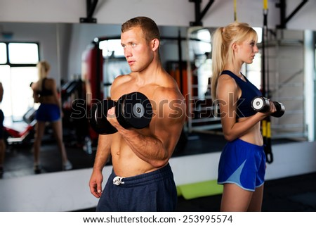 Young couple training at gym with dumbbells