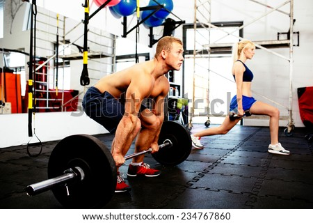 Young couple training with weights at gym - stock photo