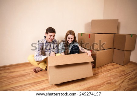 young couple unpacking boxes in a living room